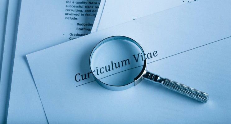 magnifying glass on a stack of papers. top paper reads 'Curriculum Vitae'.